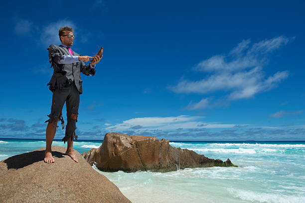 castaway businessman uses coconut smartphone on beach - desert island stock photos and pictures