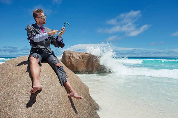 castaway businessman uses flip-flip smartphone on beach - desert island stock photos and pictures