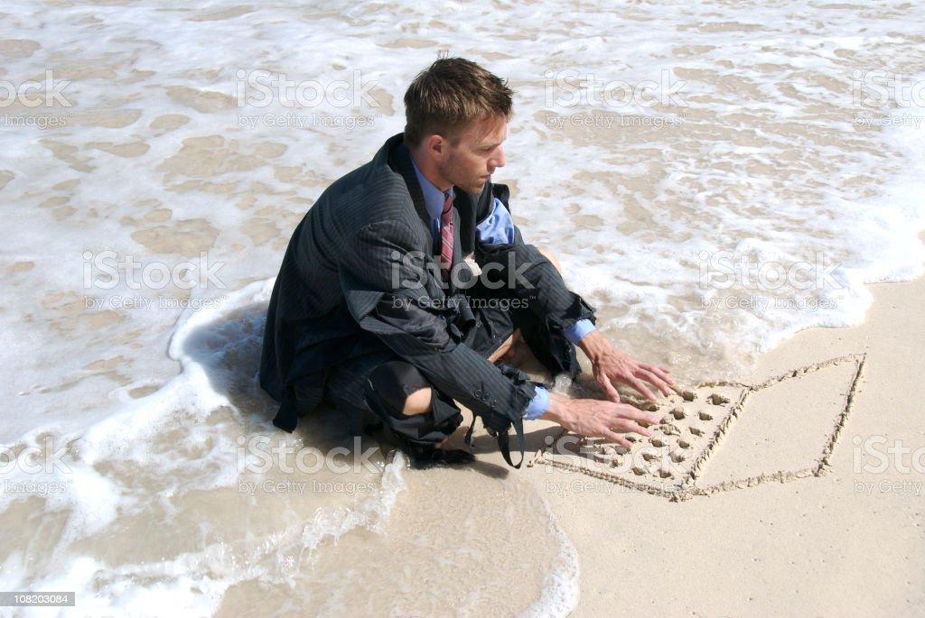 Castaway Businessman Using Sand Drawn Laptop stock photo