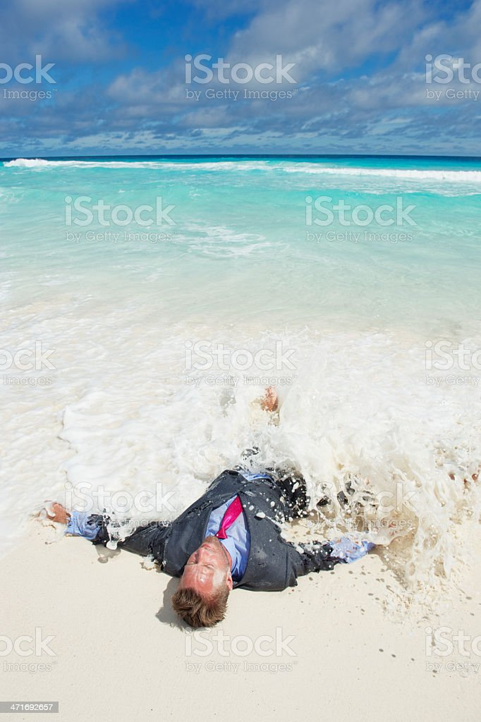 Castaway Businessman Washes Ashore in Wave on Tropical Beach royalty-free stock photo