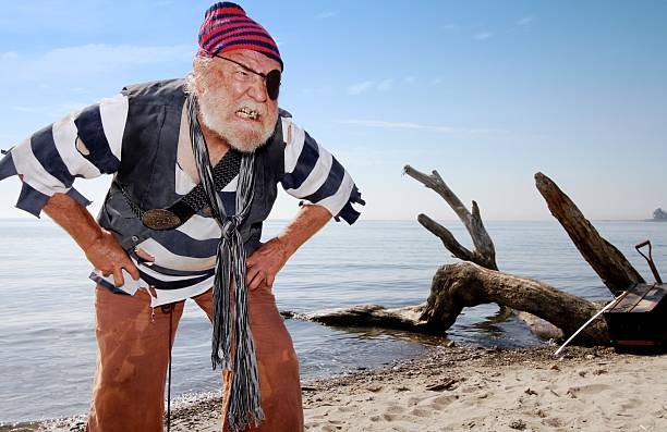 Castaway pirate defends treasure chest Ragged castaway pirate on beach bares his teeth and leans forward, defending treasure chest nearby. costume eye patch stock pictures, royalty-free photos & images