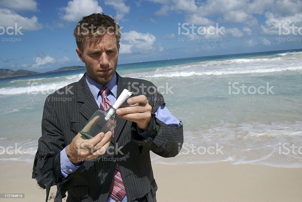 Castaway Puts Message into a Bottle royalty-free stock photo