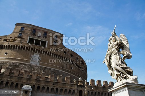 Rome, Italy - May 28, 2016:  The famous Castel Sant Angelo in Rome Italy along with one of the angle statues that line the Ponte Sant Angelo.