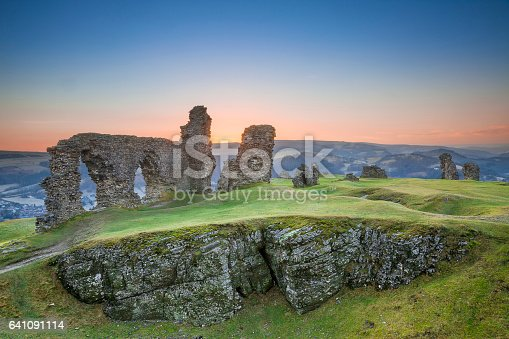 The Castell Dinas Bran, or Crow Castle in English, in Wales at sunset. These ancient ruins are all is left of a mighty castle that once stood on top of the hillside near the city of Llangollen, Wales, UK.