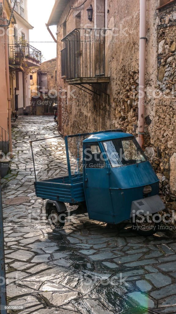 Castelmola, Taormina, Messina. March 2017: traditional vintage vehicle with three weels and blue metal paint, called Ape car,  parked on the street, next to a rural house with big stone wall. - foto stock