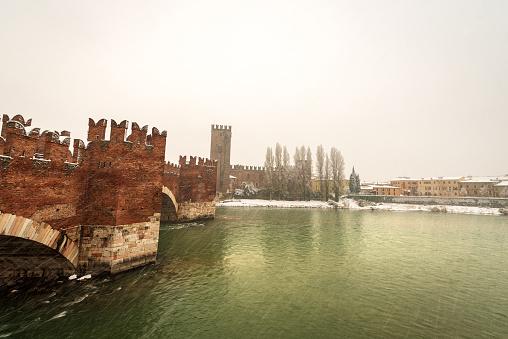 Verona. Ponte Scaligero (medieval bridge) and Castelvecchio (Old Castle) with the River Adige in winter while it snows. UNESCO world heritage site, Veneto, Italy, Europe