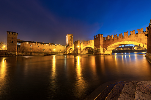 Verona, Veneto, Italy - December 8th, 2012: The Castelvecchio bridge at night (italian: Ponte di Castelvecchio) or Scaliger Bridge (Italian: Ponte Scaligero) is a fortified bridge in Verona over the Adige river, near Castelvecchio (Old Castle), the castle of Verona (UNESCO world heritage site), It is the most important military construction of the Scaligera dynasty that ruled the city in the Middle Ages. Castelvecchio is now home to the Castelvecchio Museum.