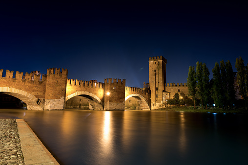 Verona, Veneto, Italy - November 15th, 2012: The Castelvecchio bridge at night (italian: Ponte di Castelvecchio) or Scaliger Bridge (Italian: Ponte Scaligero) is a fortified bridge in Verona over the Adige river, near Castelvecchio (Old Castle), the castle of Verona (UNESCO world heritage site), It is the most important military construction of the Scaligera dynasty that ruled the city in the Middle Ages. Castelvecchio is now home to the Castelvecchio Museum.