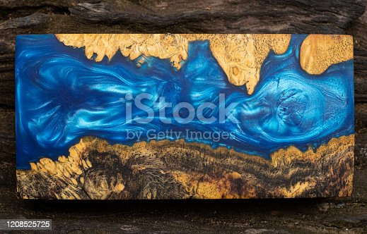 527567107 istock photo Casting blue epoxy resin burl wood cube on old table art background, Nature Afzelia wooden 1208525725