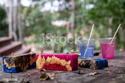 527567107 istock photo Casting green epoxy resin burl wood cube on old table art background, Nature Afzelia wooden 1203743748
