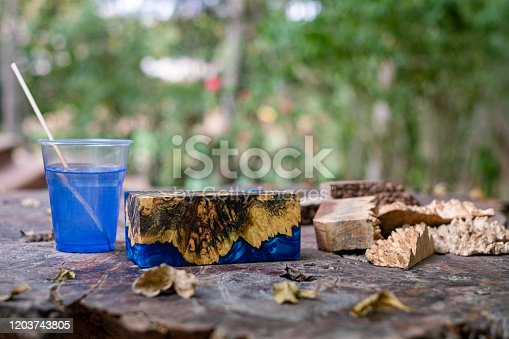 527567107 istock photo Casting green epoxy resin burl wood cube on old table art background, Nature Afzelia wooden 1203743805