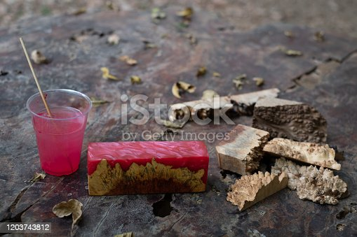 527567107 istock photo Casting red epoxy resin burl wood cube on old table art background, Nature Afzelia wooden 1203743812