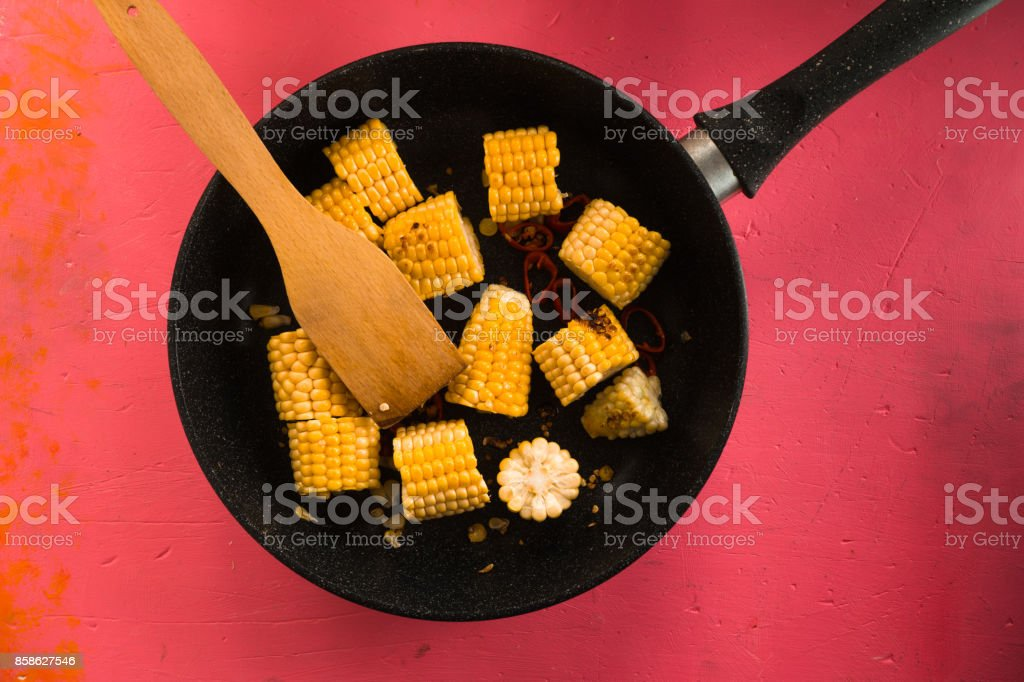 Cast-iron frying pan with pieces of corn on a pink table stock photo
