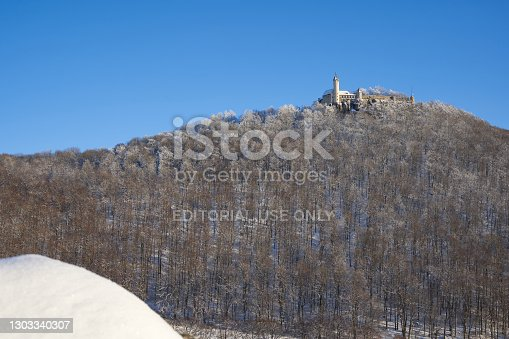 Owen, Germany - February 19, 2021: Castle also Stronghold (Teck) in winter on a clear evening with blue sky, many trees on the hill, small rock with snow in the foreground. Germany, Owen, Swabian alb.