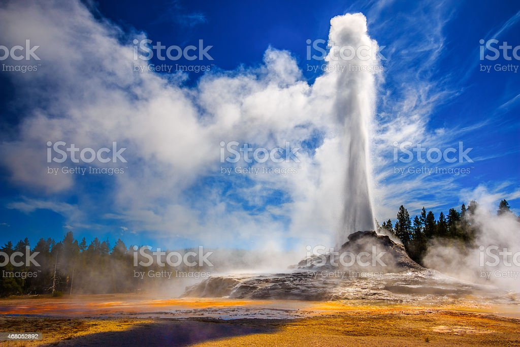 Castle Geyser erupting in Yellowstone Castle Geyser erupting in Yellowstone in strong back light. Yellowstone National Park Stock Photo