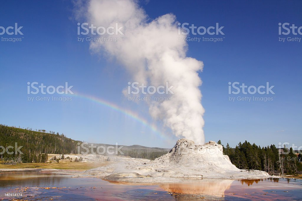 Castle Geyser with white smoke and rainbow sky background stock photo