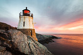 Small Castle Hill Lighthouse sits on the rocky coastline of Newport, Rhode Island at sunset with the waves slowly rushing across the rocks.