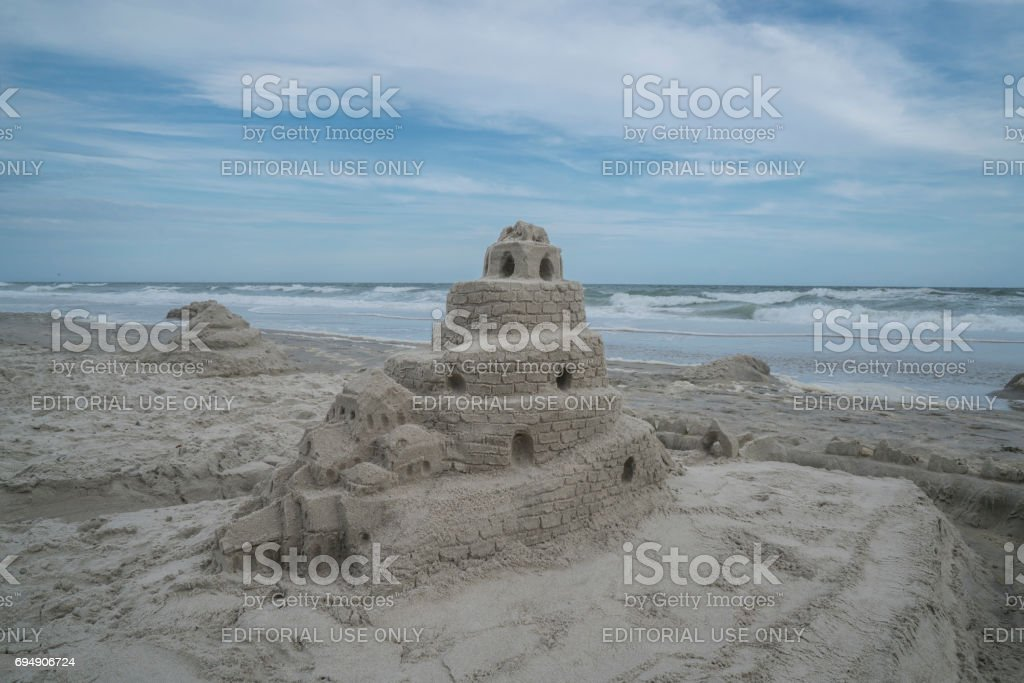 Sand castle built by few boys on the beach is standing firmly despite...