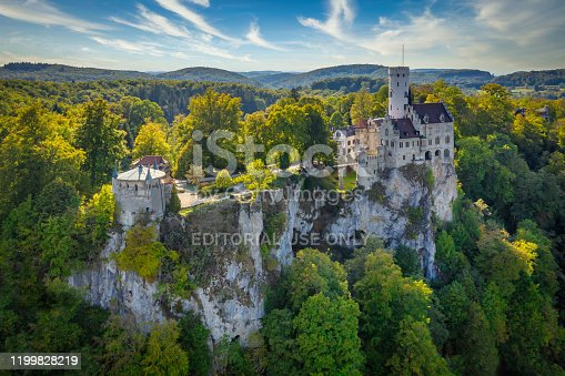 Honau - Reutlingen, Germany - September 30th, 2018: Aerial drone point of view over the Swabian Jura - Schwäbische Alb - with beautiful fairy-tale Castle Lichtenstein on top a steep rock a sunny late summer day. Unrecognizable tourists and visitors of from above. Swabian Alb, Reutlingen, Baden Wurttemberg, Germany