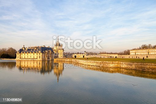 Chantilly, France - February 16 2019: The Castle of Chantilly reflecting in the moat with the Castle of Enghien on the other side of the Terrace of the Constable.