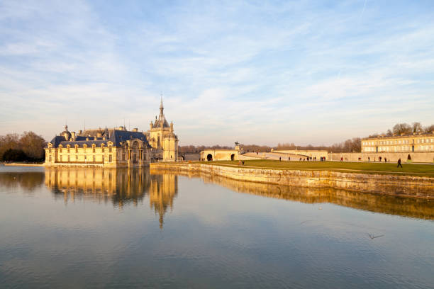 Castle of Chantilly and Enghien Chantilly, France - February 16 2019: The Castle of Chantilly reflecting in the moat with the Castle of Enghien on the other side of the Terrace of the Constable. hauts de france stock pictures, royalty-free photos & images