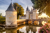 France - Sept 21, 2013: Castle or chateau of Sully-sur-Loire at sunset. This old castle is a famous landmark in France. Beautiful sunny view of the French castle on the water. Fairytale medieval castle in summer.