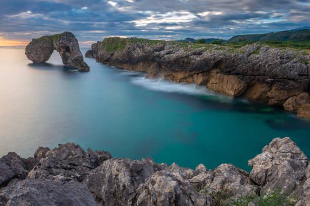 Rocha de Castro de Las Gaviotas no nascer do sol, Asturias, Spain - foto de acervo