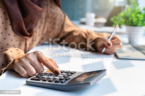 istock Casual accountant or banker woman hand using calculator at workplace. 1160969401