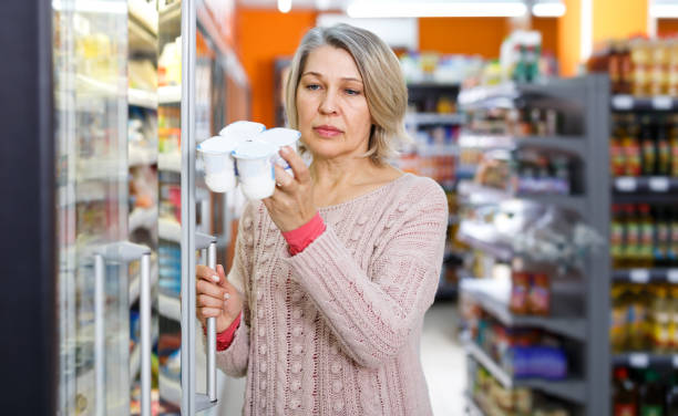 Casual adult woman shopping for milk products stock photo