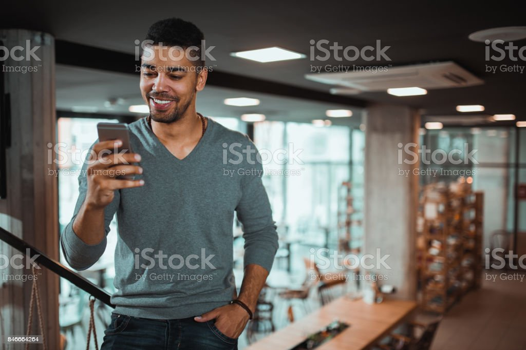 Casual African American businessman reading text message on cell phone. stock photo