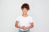 Portrait of casual afro american woman standing relaxed against grey background. Horizontal shot of african female model in t-shirt and jeans looking at camera and smiling.