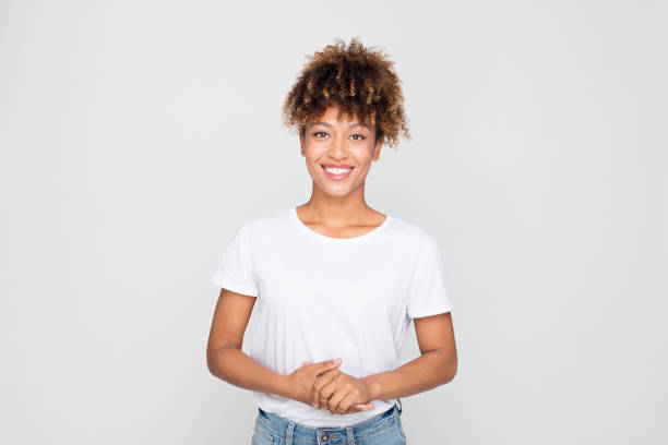 Casual afro american woman standing relaxed Portrait of casual afro american woman standing relaxed against grey background. Horizontal shot of african female model in t-shirt and jeans looking at camera and smiling. waist up stock pictures, royalty-free photos & images