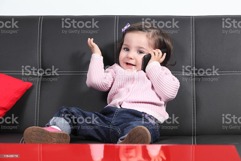 Casual baby playing happy with a mobile phone stock photo