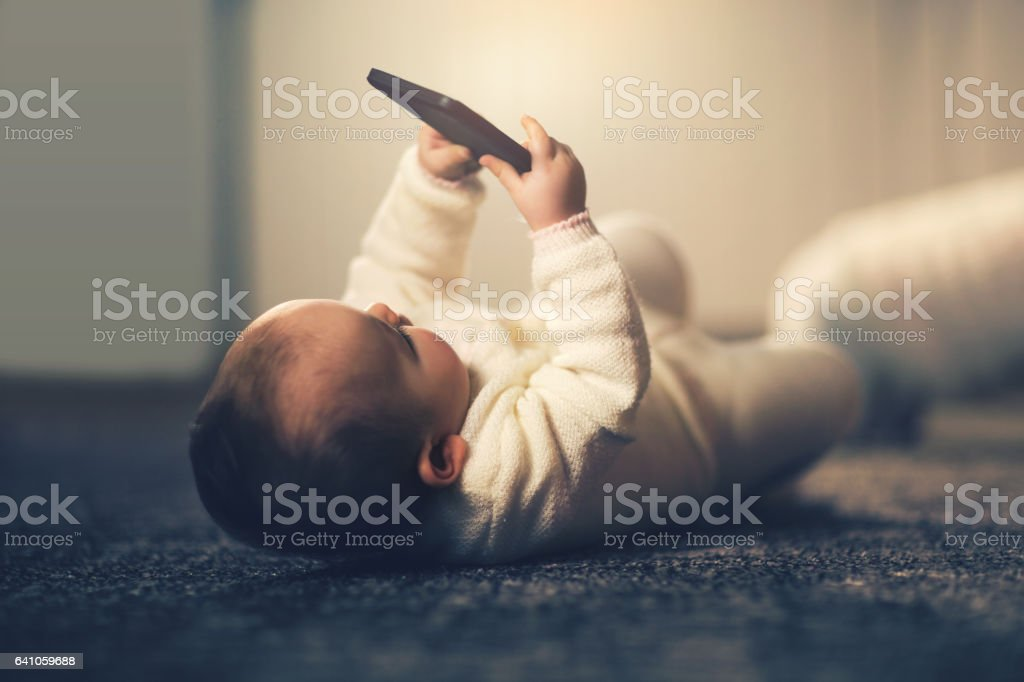 Casual baby watching a mobile phone stock photo