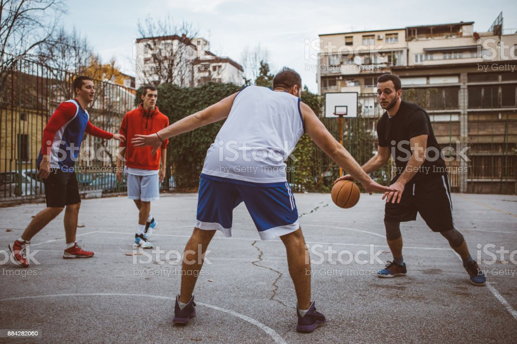 Group of male friends playing basketball at city court
