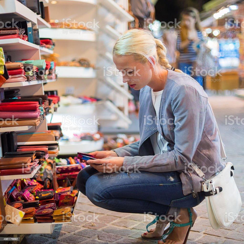 Lässig Blonde Frau shopping für Brieftasche aus Leder. – Foto
