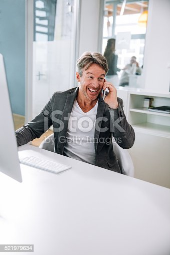 513583458 istock photo Casual business man chatting on smartphone while laughing in office 521979634