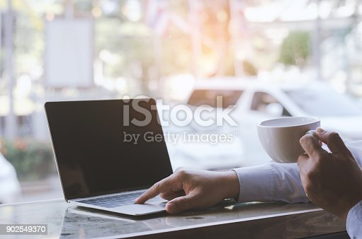 casual business man or freelance working on computer laptop and typing on keyboard and holding coffee cup on the desk in coffee shop.