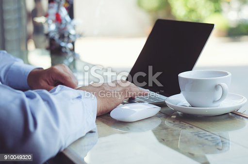 casual business man or freelance working on computer laptop and typing on keyboard with coffee cup on the desk in coffee shop.