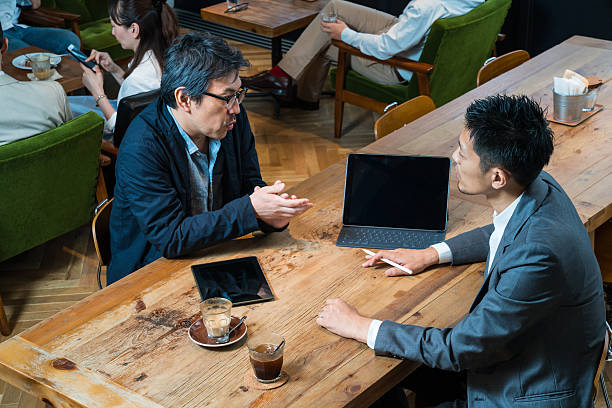 Casual business meeting in cafe with a large digital tablet Casual business meeting in a cafe with a large digital tablet only japanese stock pictures, royalty-free photos & images