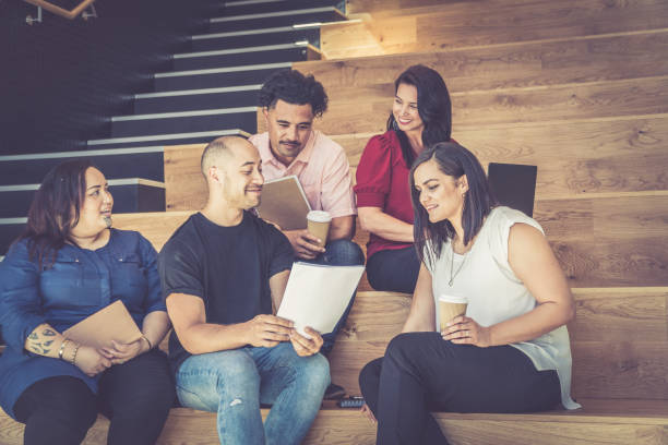 casual business meeting on stairs - pacific islander ethnicity stock photos and pictures