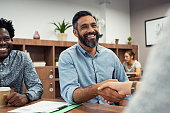 Two business people shaking hands while sitting in meeting room. Middle eastern businessman shake hands to businesswoman. Portrait of happy smiling latin man signing off deal with an handshake.