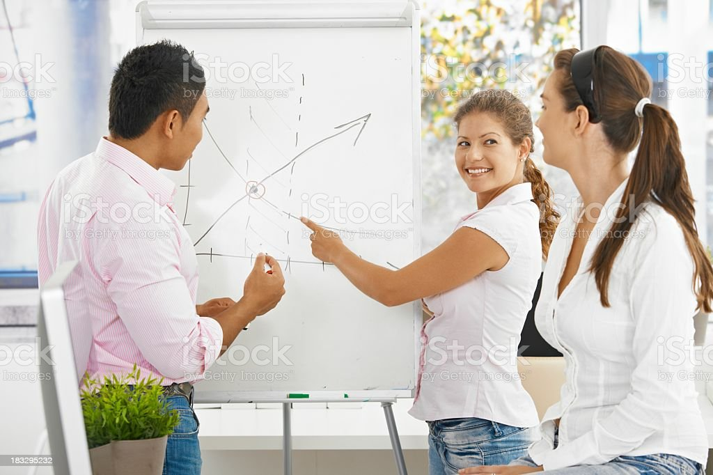 Casual business people talking in front of whiteboard royalty-free stock photo