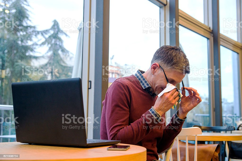Casual Businessman cleaning eyeglasses with his laptopn on table Lizenzfreies stock-foto