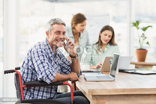 istock Casual businessman in wheelchair phoning 668536594
