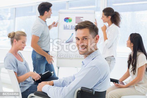 660681964istockphoto Casual businessman in wheelchair smiling at camera during presentation 842044454