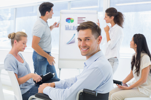 660681964 istock photo Casual businessman in wheelchair smiling at camera during presentation 842044454