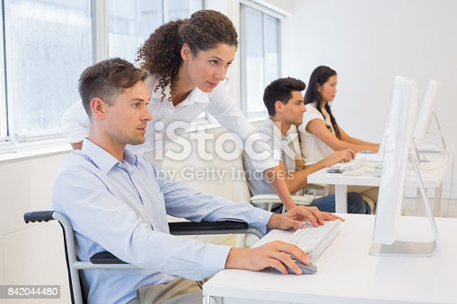 istock Casual businessman in wheelchair working at his desk with colleague 842044480