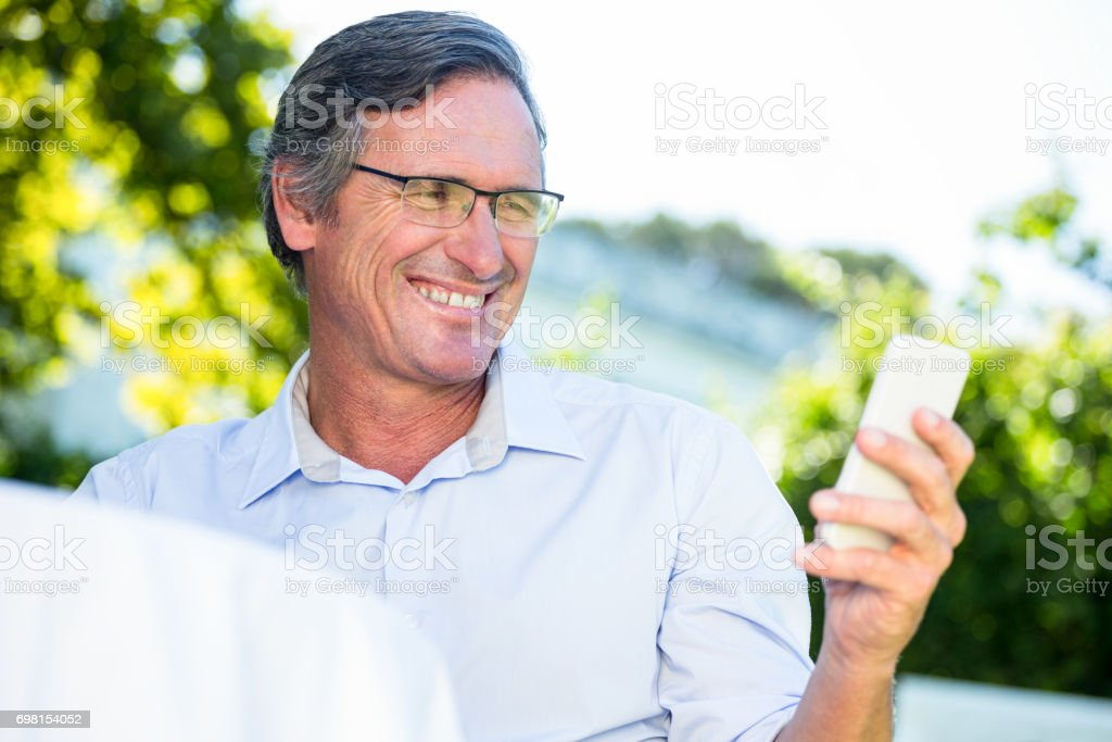 Casual businessman looking at smartphone smiling stock photo