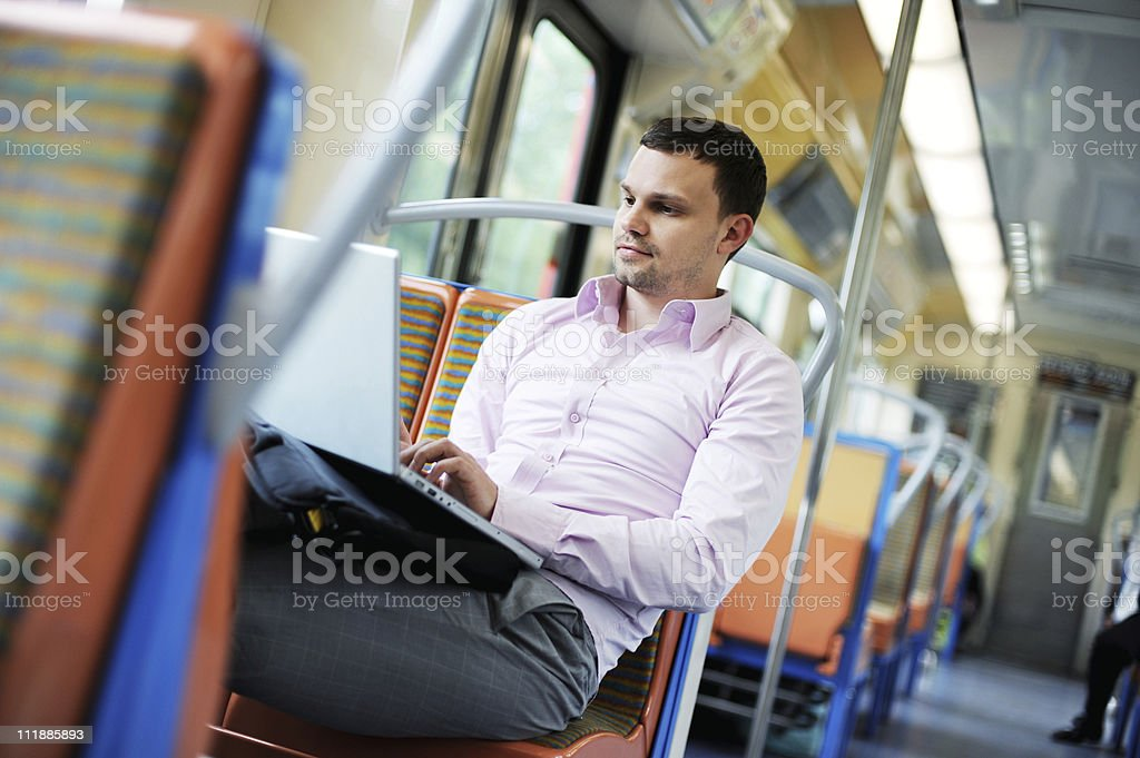 Casual Businessman on Train with Laptop Computer stock photo